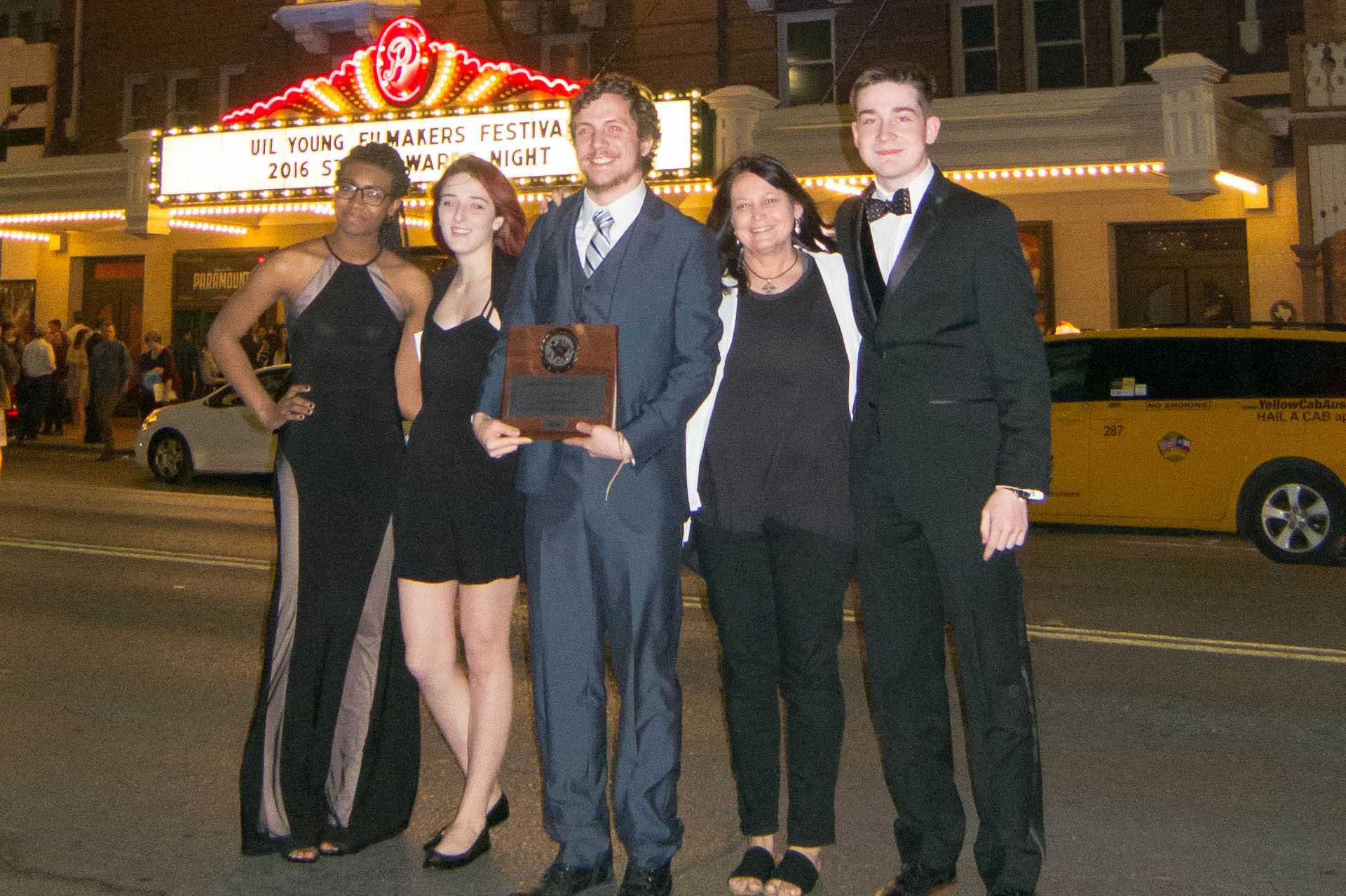 From left to right: Alexandria Dave, Daryn Crowninshield, Brett Bellamy, Coach Bradford, and Cole Andrews pose with their award in front of the Paramount Theatre in Austin, Texas.